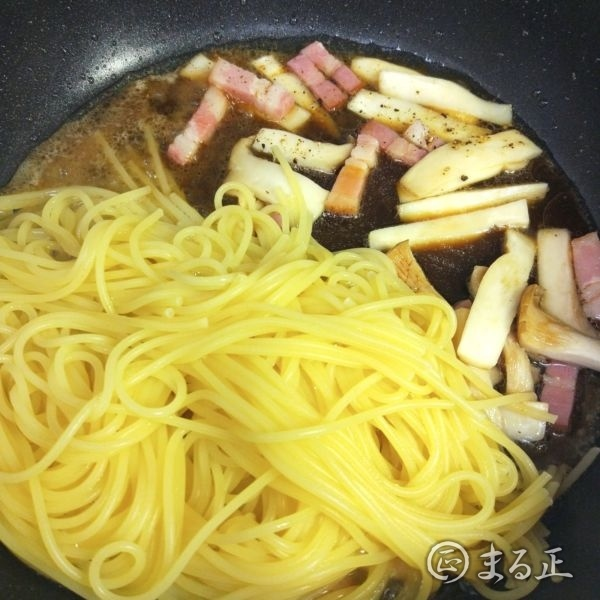 写真:パスタ麺と調味料を加える