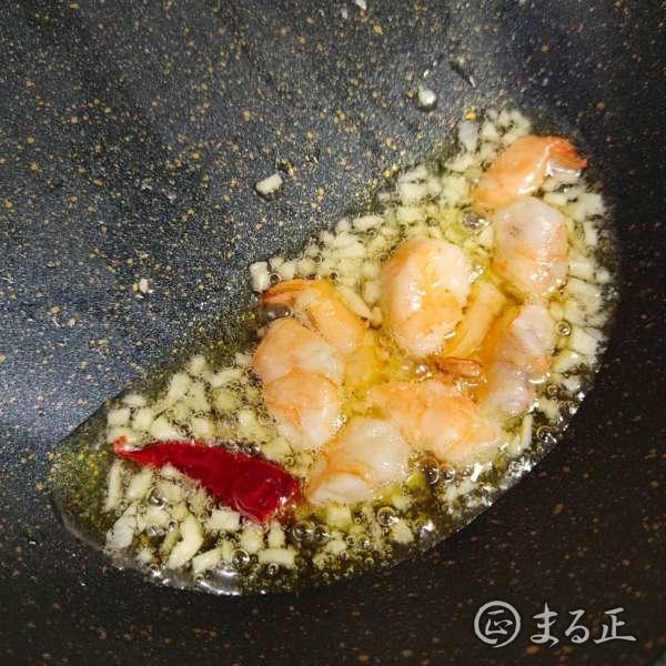 写真:ニンニク、海老、鷹の爪をオリーブオイルで炒める