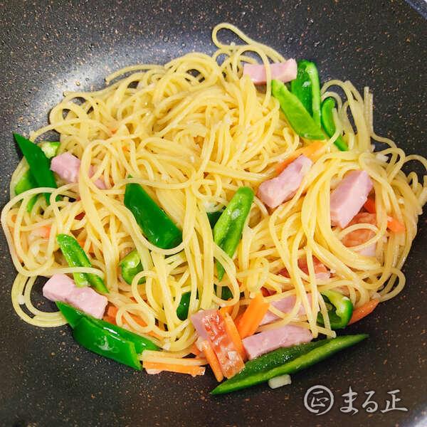 写真:野菜とパスタを加えて炒める